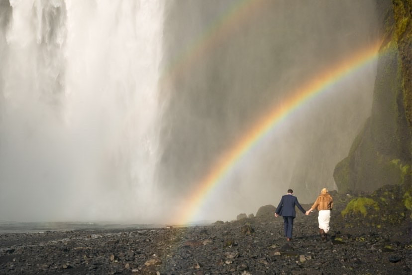 Newlyweds walking towards Skogafoss waterfall for wedding photos