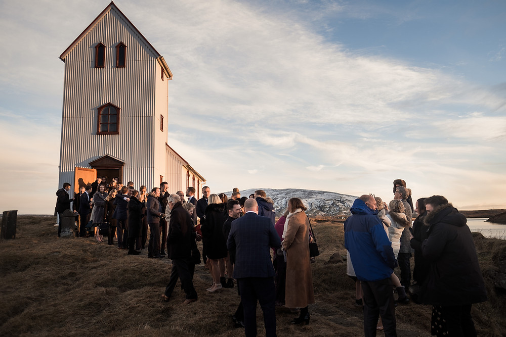 Iceland Wedding guests gathered outside Lakeside church Ulfljotsvatnskirkja. Photo by Nordica Photography