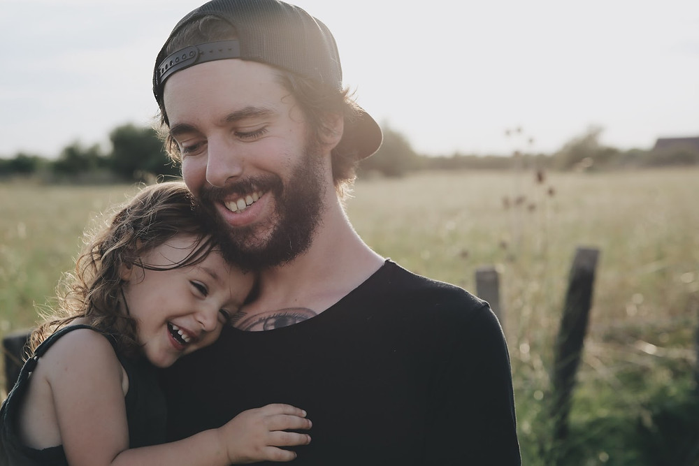 Father holding his daughter and smiling