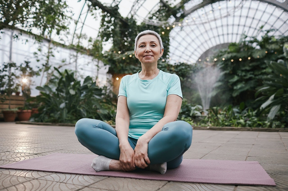 Woman sitting in a greenhouse meditating