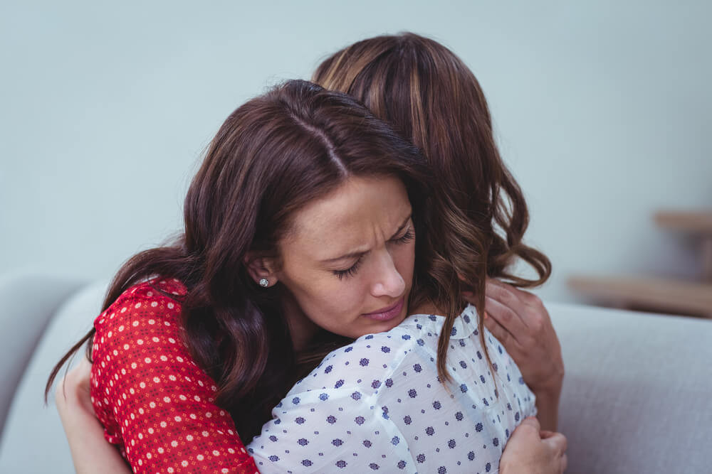 Mother comforting grieving daughter