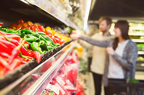 Consumers in supermarket looking at fresh vegetables