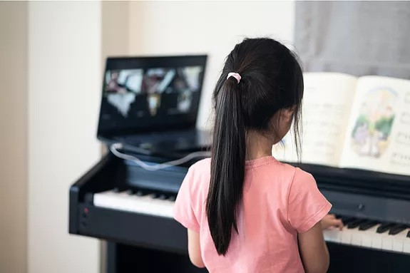 Girl learning piano online
