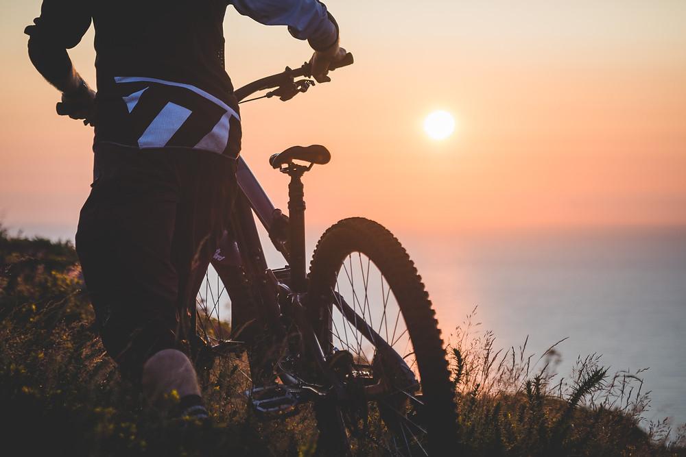 mountain biker walking towards sunrise, colm keating,