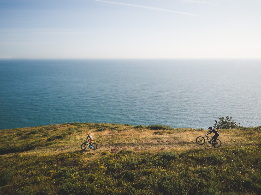colm keating mountain bikers ride down cliff with sea in background, iosac coleman, john belling,