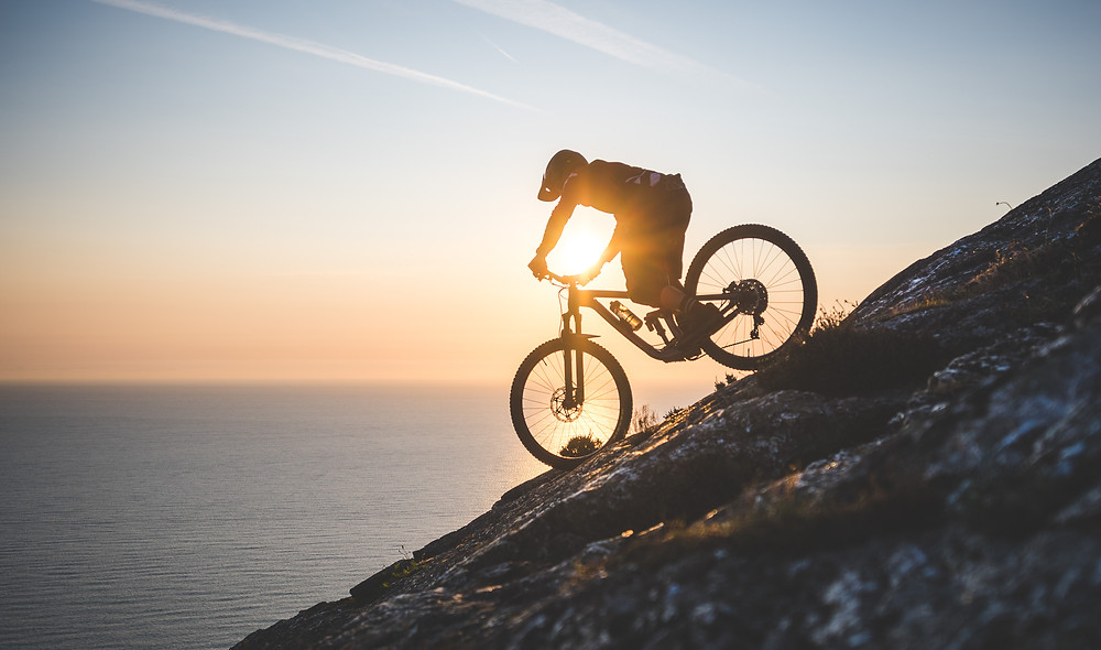 mountain biker rides down cliff at sunrise, bray head, colm keating, john belling,