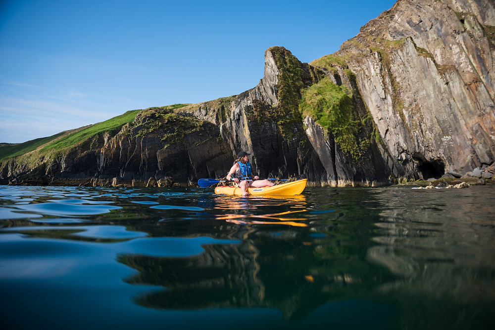 kayak with reflection alongside cliff, colm keating,