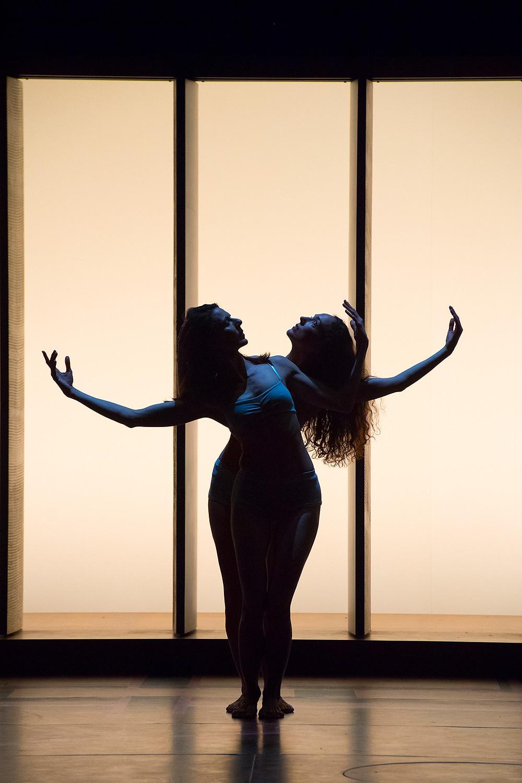 フィリップ・ドゥクフレ『新作短編集』より白いライトの前で重なるようにダンスする2名の女性の写真