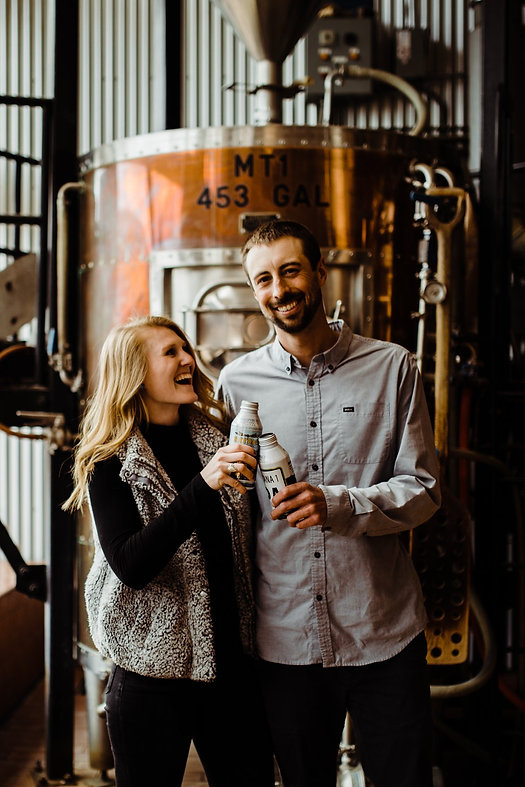 Engagement photo of smiling couple in a brewery