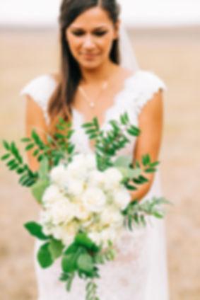 Wedding Portrait of Bride looking at wedding bouquet
