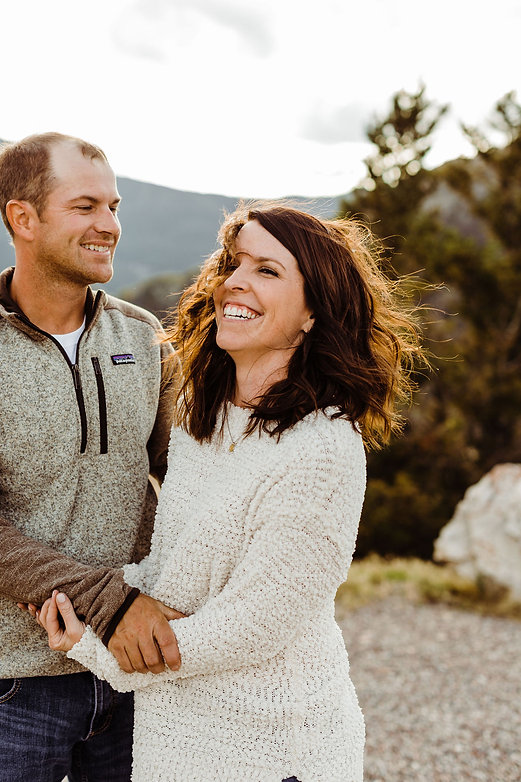 Engagement photo of couple laughing on mountain during golden hour