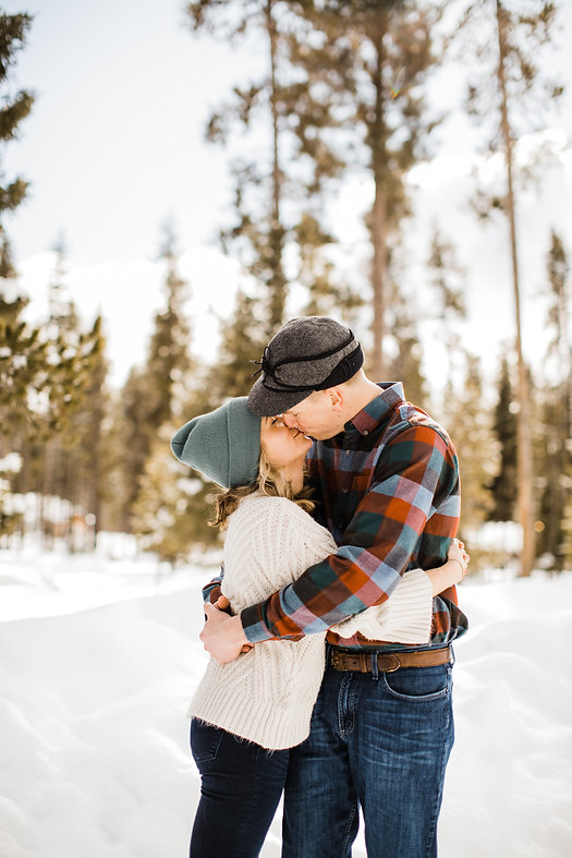 Engagement Photo of couple kissing in the snow