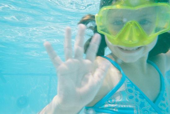 Little girl swimming underwater in clean pool