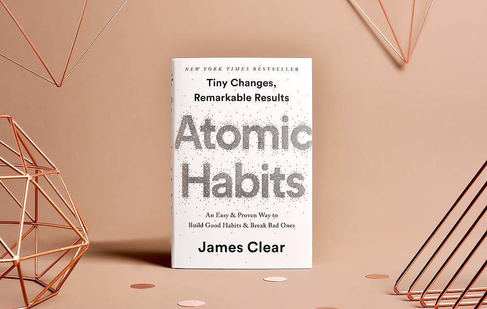 A white book with the words Atomic Habits sits in a beige setting with copper objects scattered around at the periphery