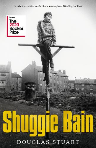 A young boy sits on top of a road sign staring into the distance. The background shows run down housing in black and white, the title of the book Shuggie Bain is displayed on the cover along with authors name Douglas Stuart. The image also bears the Booker Prize 2020 logo