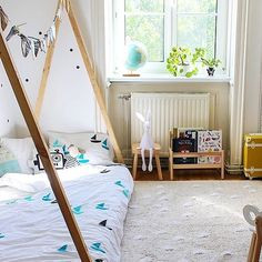 A sunny childrens bedroom full of light. A low camp bed with wooden canopy features a bedding set with blue flags. Next to the window a set of children's toys and books.