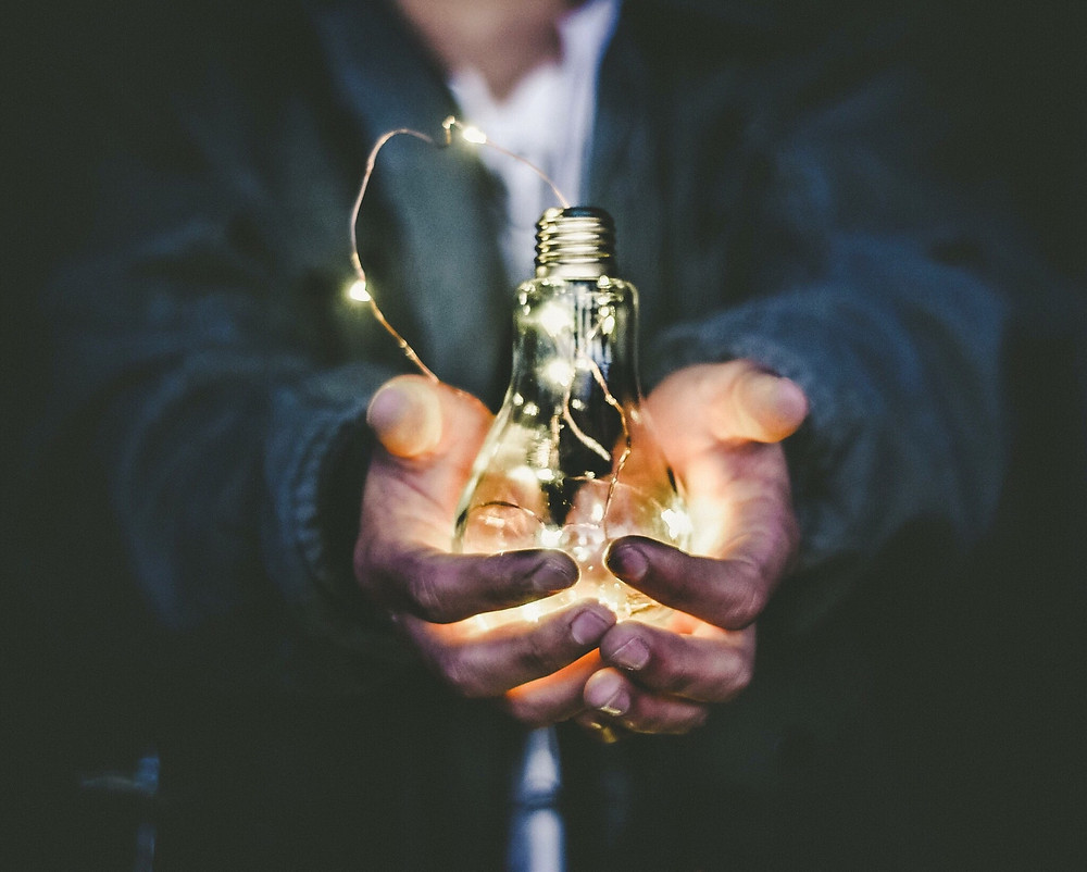 A man holds a light bulb in his hands