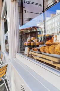Picture of a coffee shop with cakes in the window