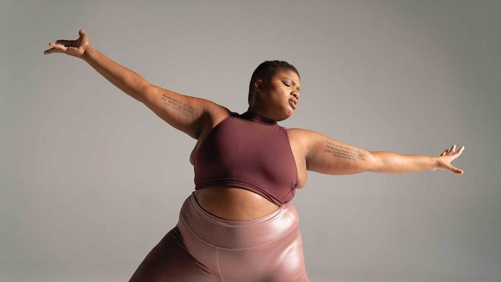Black female with tattoos on upper arms wearing yoga clothing, arms outstretched.