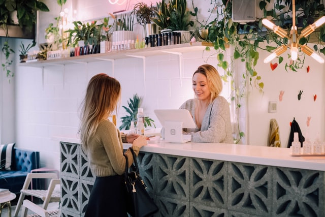 Two women in a coffee shop standing at a till