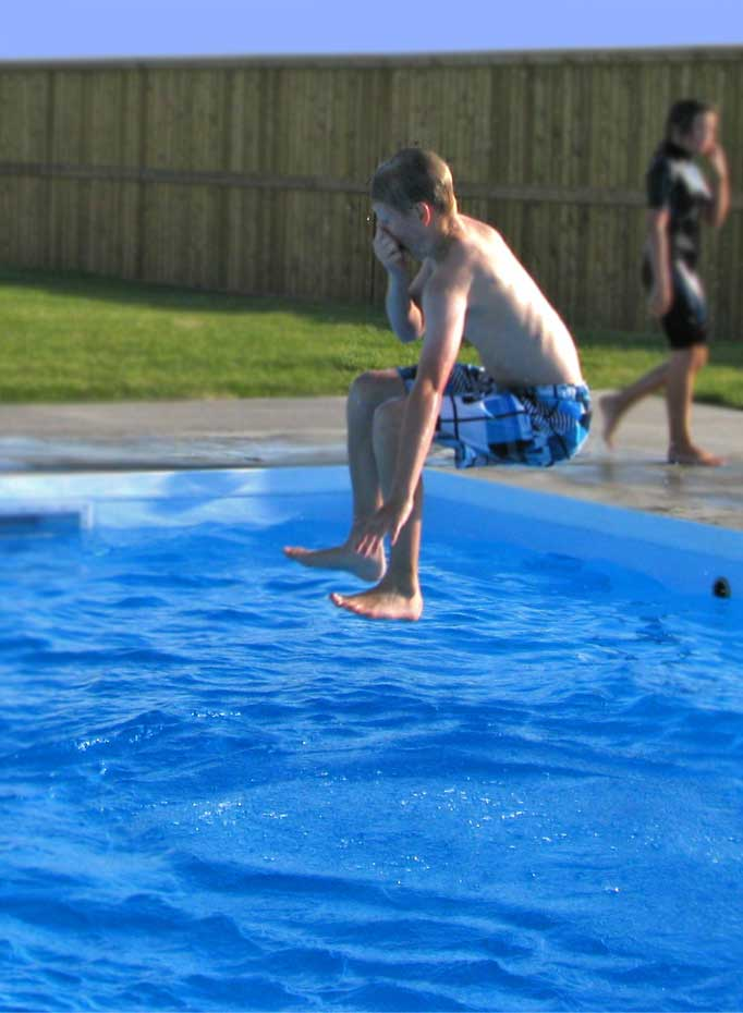 boy-jumps-into-pool-blue-su