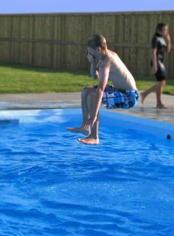 boy-jumps-into-pool-blue-su