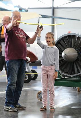 Bénévole expliquant à un enfant le vol d'un avion