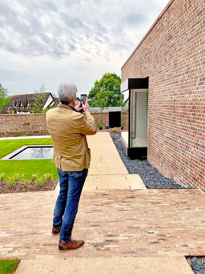 Walled Garden Farringdon (Para 79/55), Design Review Panel Post completion Site Visit - Panel member taking a photograph of the front elevation