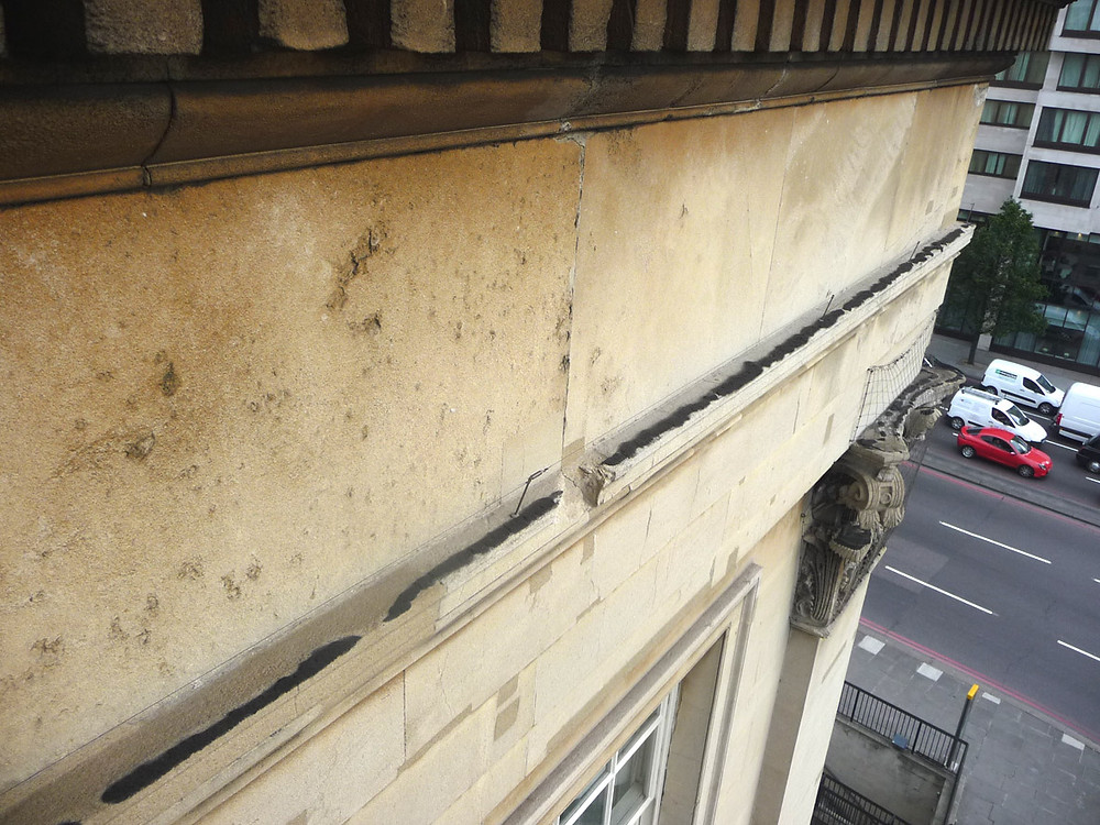 Soiling on top of the string course at high level. Note the pollution crusts to the dentil course, the damaged string course and the plastic repairs carried out in a lime based mortar that does not match the colour of the existing stone