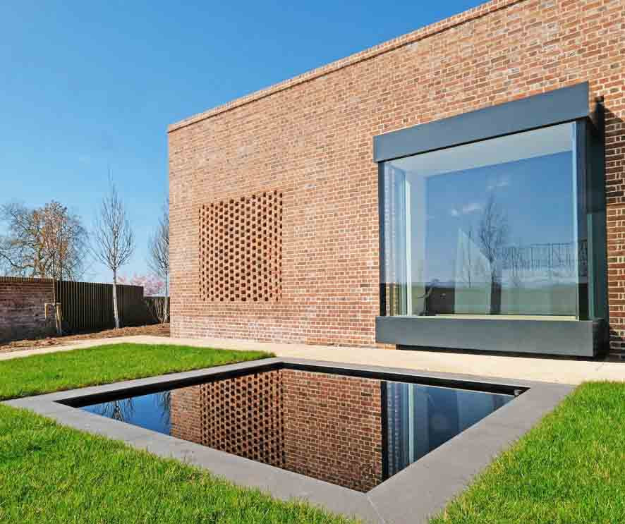 Walled Garden Farringdon (Para 79/55), Design Review Panel Post completion Site Visit - Square bay window reflected over pond to the fornt elevation