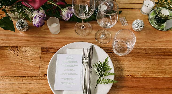 set table, purple toned blooms, glassware, white crockery