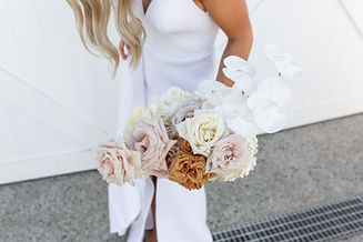 blode woman wearing white dress holds light coloured bouquet