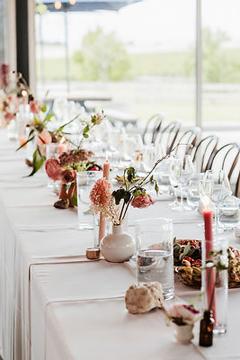 wide shot up reception table - white cloths, peach pink florals, pink taper candles