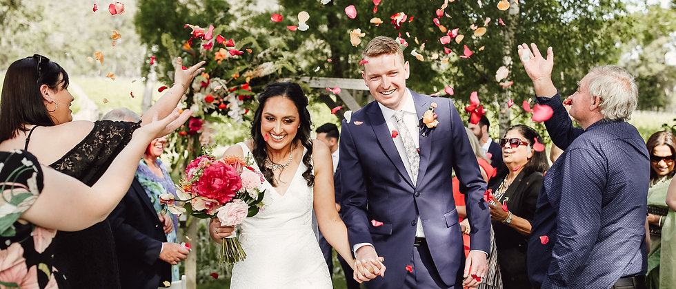 couple smiles as their family and friends throw petals around them