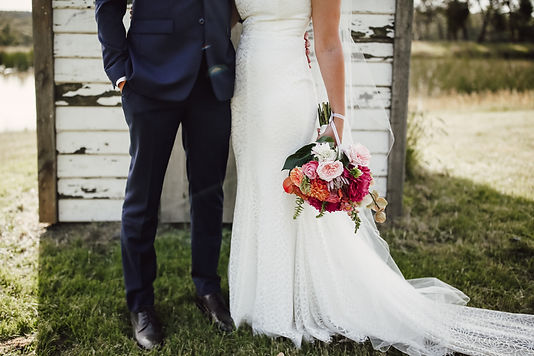 Couple stands close together, bright bouquet held down