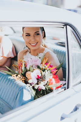 woman sits smiling in car, holding brightly coloured tropical bouquet