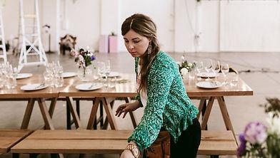 brunette woman sets table, weraing teal green jacket