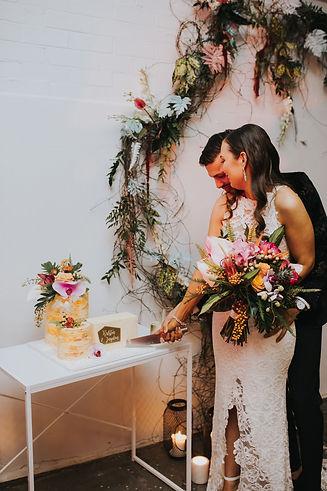 couple cuts wedding cake, bride holding bouquet