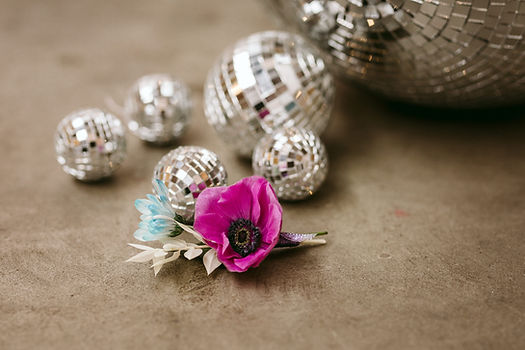 teal blue purple buttonhole sits amongst disco ball ornaments of varying sizes