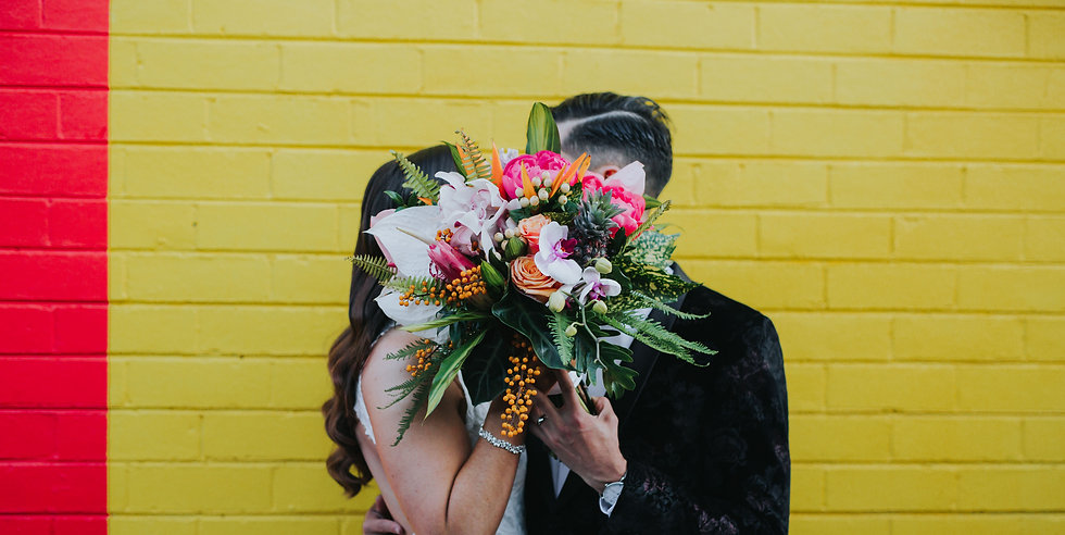 couple stands in front of yellow brick wall, sharing a kiss behind a tropical bouquet