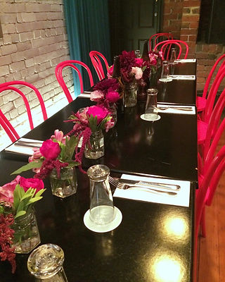 wide shot, black table, red bentwood chairs, bright red and pink blooms up centre of table
