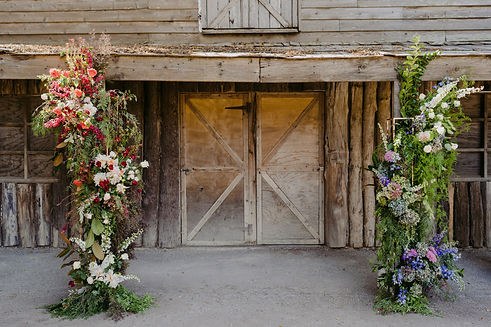 red, peach, blue, green, purple oversized floral arrangement stands in front of barn