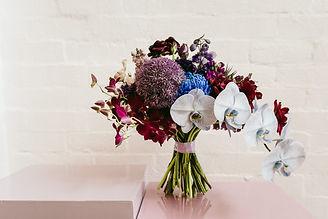 blue purple toned bouquet stands on light purple plinth