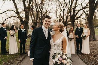 Couple standing smiling together, their wedding party standing behind them