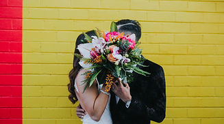 A couple stands in front of a yellow wall, sharing a kiss behind their bouquet