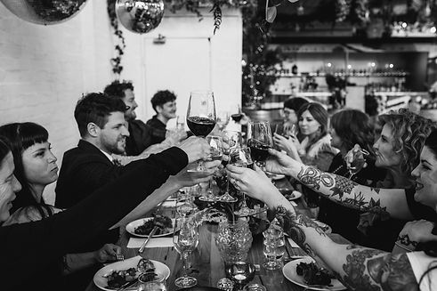 group of people sit at table and raise their wine glasses together