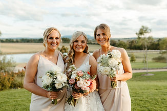 bride and her two bridesmaids hold their bouquets, smiling at the camera