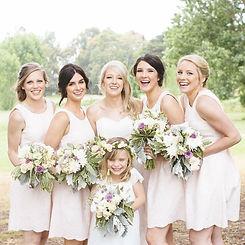 5 women and one flower girl, all wearing cream dresses