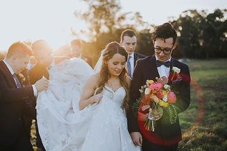 couple walks together, groom holding bouquet, groomsmen carrying bride's skirt