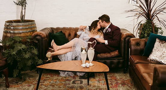 couple embraces, reclining on brown leather couch